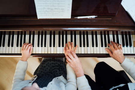 a music teacher with the pupil at the lesson piano, top view Stok Fotoğraf
