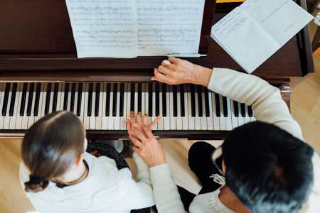 a music teacher with the pupil at the lesson piano, top view