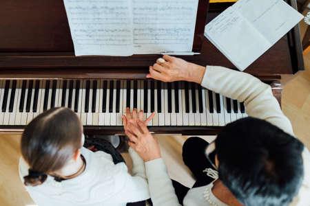 muziekleraar met de leerling bij de les piano, bovenaanzicht Stockfoto