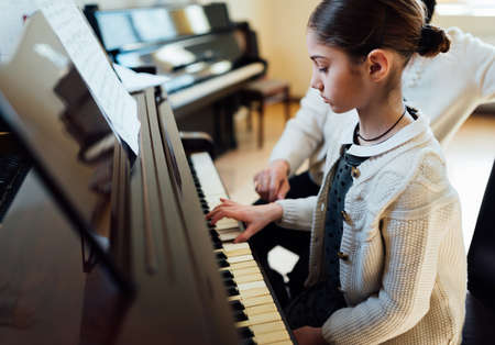 a music teacher with the pupil at the lesson piano 写真素材