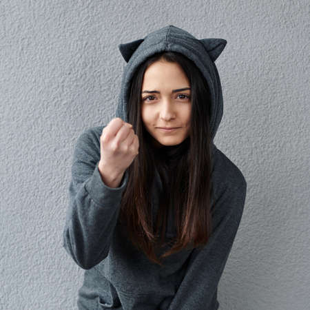threatens: cheerful teenager girl threatens fist Stock Photo