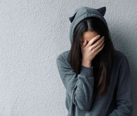 Sad woman in grey hoodie with cats ears covering face with hand. Wall background.