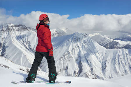 she: snowboarder in a red jacket on the edge of a cliff. She turns around smiling.