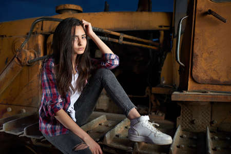 old tractor: beautiful teen girl sitting on an old tractor tracks.