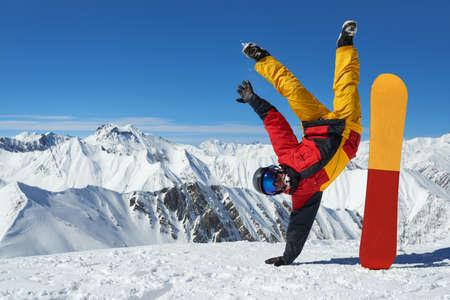 montañas nevadas: snowboarder Alegre, por un lado, cerca de colorido tablero contra de montañas nevadas y cielo azul