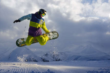 scatters: snowboarder does the jumping trick. snow scatters pieces of mountains in the background. Stock Photo
