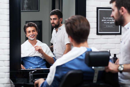 The happy client satisfied of the design of the beard and smile with barber Stock Photo