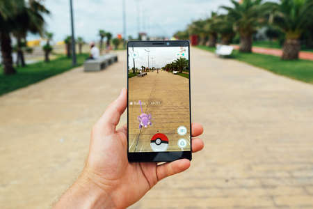 BATUMI, GEORGIA- JULY 14, 2016: Hand holding a smartphone to play the game of Augmented Reality Pokemon go