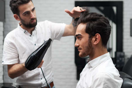 The satisfied client is sitting in the salon and drying his hair in hairdo