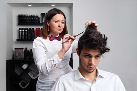 the professional hairstylist is brushing the clients hair with brush and making nice hairdo photo