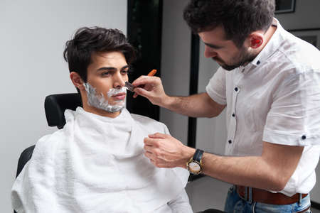 The barber carefully shaves clients beard and mustache in the barber shop