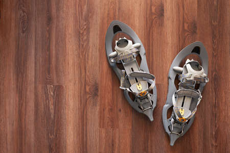 snowshoes: gray snowshoes  on the wooden floor with copyspace