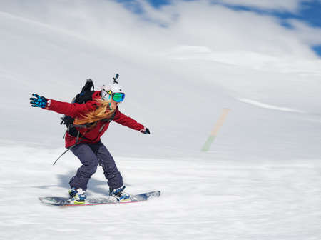 goes: girl snowboarder goes quickly down the slope and shouts his arms to the side