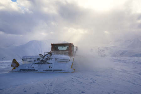 snow grooming machine: snowcat rides to work in the evening at sunset