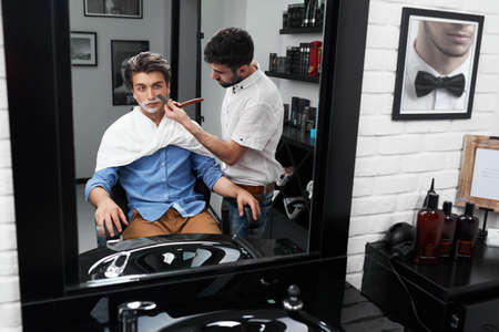serves: through a mirror, barber serves customers in the salon Stock Photo