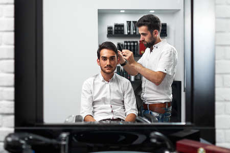 carefully: the hairstylist is carefully brushing the clients hair in the barbershop in reflection in the mirror Stock Photo
