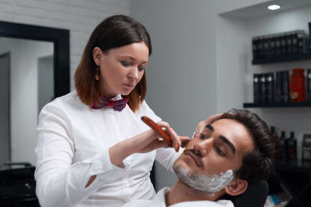 The barber woman carefully shaves clients beard in the barber shop