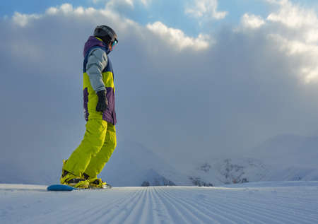 machined: snowboarder standing on the board in the mountains of freshly machined track and looking to the side, copyspace