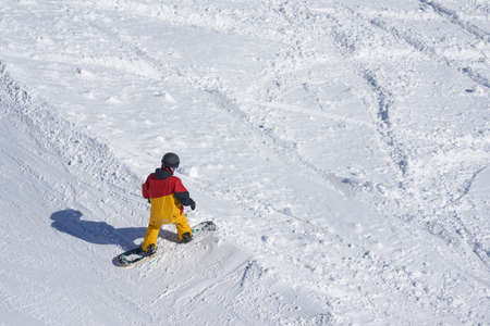 off track: freeride snowboarder kicks off the track, standing and looking down. View from above. Stock Photo