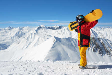 put away: snowboarder put a board on his back and looking away in the winter mountain ridges