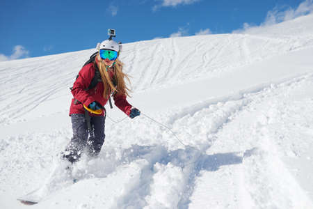 rides: girl snowboarder rides a snowboard towed holding the rope. Stock Photo