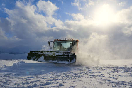 snow grooming machine: snowcat works on a slope rising in the evening air clubs of snow illuminated by the setting sunlight. Stock Photo