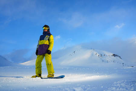 snowboarder standing on the board in the mountains of freshly machined track and looking to the side, copyspace