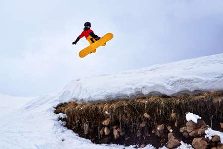 springboard: El Snowboarder que salta desde un trampolín en una colina de nieve con la hierba. Foto de archivo