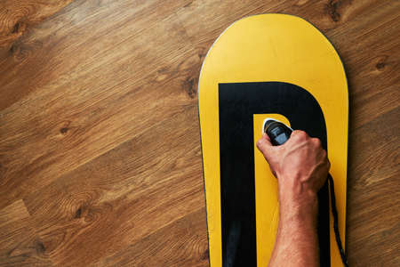ironed: man ironed wax on a snowboard, lying on the wooden floor