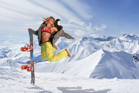 bikini top: Smiling woman with snowboard jumping in mid air against of snowy mountains.Wearing bikini top and winter sportswear.