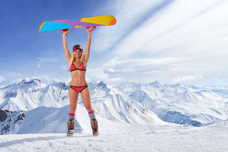 arms above head: smiling unrecognizable blonde girl in bikini swimsuit with snowboard in outstretched arms above head against of snowy mountains in sunlight