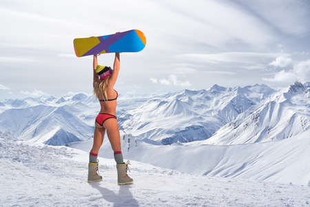 arms above head: Back view of unrecognizable blonde girl in bikini swimsuit with snowboard in outstretched arms above head against of snowy mountains in sunlight
