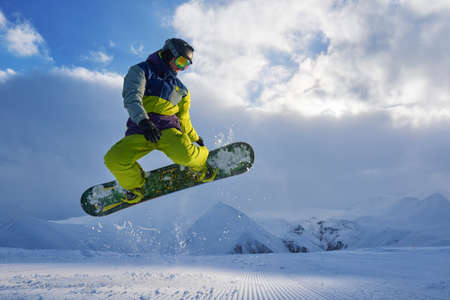 snowboarder does the jumping trick. snow scatters pieces of mountains in the background. Stock Photo
