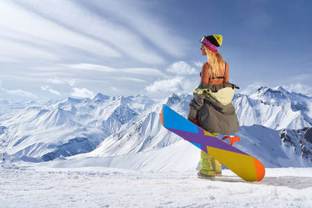 bikini top: Back view of blonde woman in bikini top with snowboard against of beautiful mountain chain covered with snow
