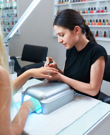 shellac coating procedure. manicure nail paint shellac, hand rests in the lamp for hardening lacquer.