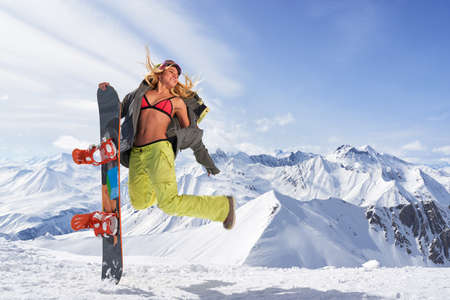 mid air: Smiling woman with snowboard jumping in mid air against of snowy mountains.Wearing bikini top and winter sportswear.