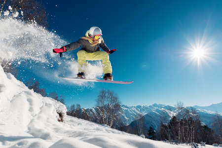 Girl is jumping with snowboard from the hill Stock Photo