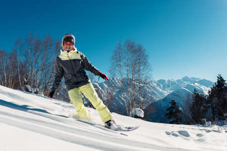wintersport: girl is riding on snowboard from hill and smiling