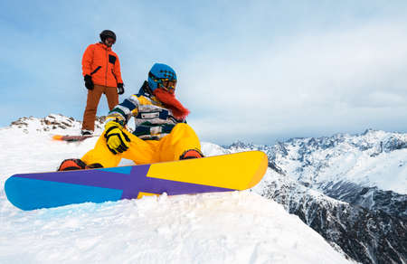snowboarders having a rest on the mountain and watching the view Stock Photo