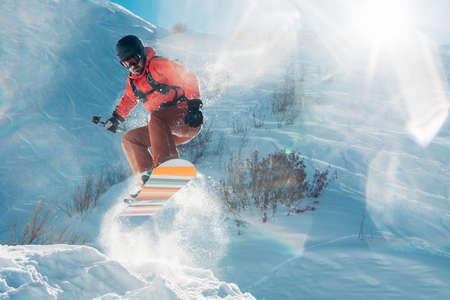 snowboarder is riding with snowboard from snow mountain in the sun beam