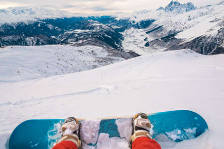 horizont: snowboarder with snowboard is sitting on the mountain and watching the beautiful mountain view