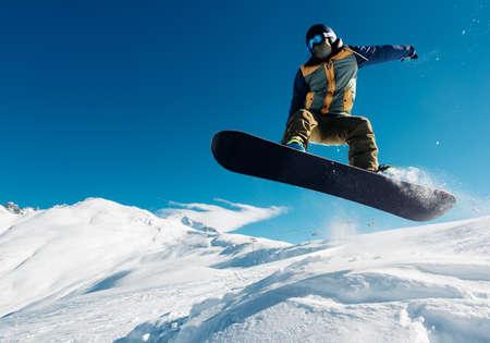 スノーボーダーは、非常に高いスノーヒルからスノーボード ジャンプします。
