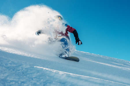 horizont: snowboarder is riding with snowboard from powder snow hill or mountain very fast Stock Photo
