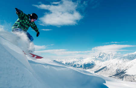 horizont: snowboarder is jumping with snowboard from snow hill in the sun beam