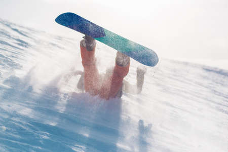 snowboarder is riding with snowboard from powder snow hill very fast and fall down 写真素材