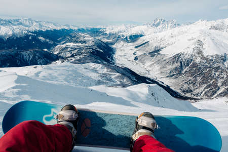 snowboarder with snowboard is sitting on the mountain and watching the beautiful mountain view