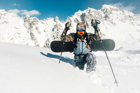 sportsman walk and fail with snowboard equipment on the snow hill and mountain range Stock Photo