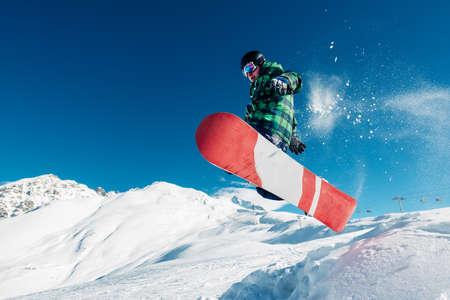 Le snowboarder saute avec snowboard de snowhill très haut