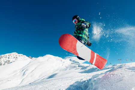 snowboarder is jumping with snowboard from snowhill very high Stock Photo
