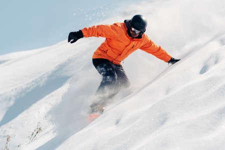 Snowboarder rijdt met snowboard van poeder sneeuw heuvel